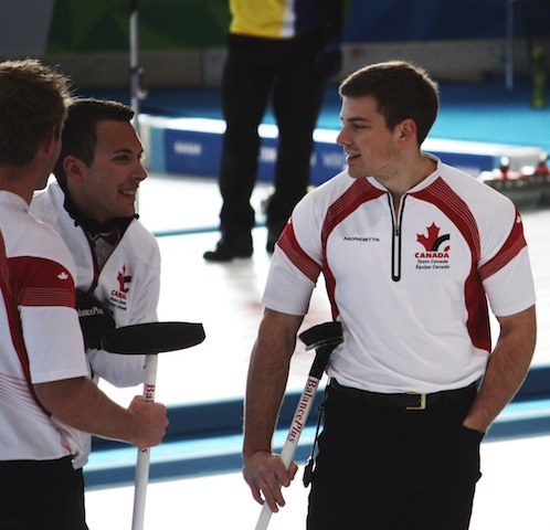 Karrick Martin (left) and Thiessen (right) chat with their Team Canada skip Brendan Bottcher during a break in the action at the Baselga di Pine Ice Stadium in Trentino, Italy (Photo R. Krepps)