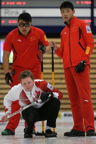 Braden Calvert guide la trajectoire d'une pierre contre la Chine au Jour 3 du Championnat mondial de curling junior à Flims en Suisse. (Photo WCF/Richard Gray)
