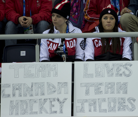 Shannon Szabados, left, and Natalie Spooner of the Canadian women 's hockey team cheer on Team Brad Jacobs on Thursday. (Photo, CCA/Michael Burns)