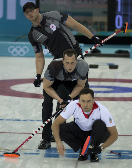 Great Britain skip David Murdoch checks out his shot with Canada's Ryan Harnden, top, and E.J. Harnden looking on.