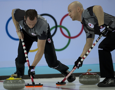E.J. Harnden d'Équipe Canada, à gauche, et Ryan Fry balayer un rocher lors de la demi-finale de mercredi.