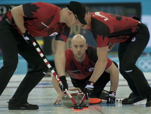 Team Canada third Ryan Fry delivers rock to sweepers Ryan Harnden, left, and E.J. Harnden. (Photo, CCA/Michael Burns)