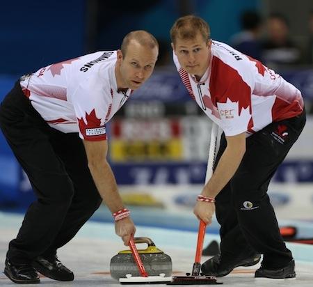 Balayeuses Équipe Canada Pat Simmons, à gauche, et Carter Rycroft recherchent des directions. (Photo, Fédération mondiale de curling / Richard Gray)