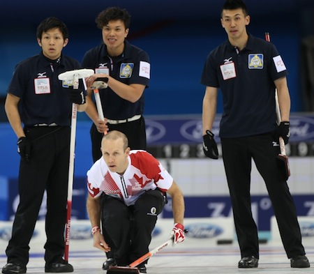 Équipe Canada vice-capitaine Pat Simmons offre son rocher que les joueurs japonais regardent. (Photo, Fédération mondiale de curling / Richard Gray)