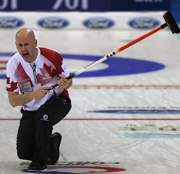 Équipe Canada capitaine Kevin Koe guide ses balayeuses lors de la victoire de dimanche sur la Chine. (Photo, Fédération mondiale de curling / Richard Gray)