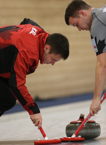 Kyle Kurz et Brendan Wilson triment dur lors du match éliminatoire Page 3 vs. 4 au Championnat mondial de curling junior 2014. (Photo WCF/Richard Gray)