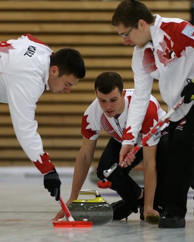 Kyle Kurz, Brendan Wilson et Lucas Van Den Bosch en action lors du match pour la médaille de bronze au Championnat mondial de curling junior 2014 à Flims en Suisse.(Photo WCF/Richard Gray)