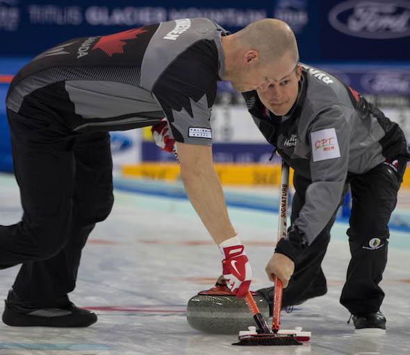Nolan Thiessen d'Équipe Canada, à gauche, et Carter Rycroft vont travailler pendant victoire sur la Russie, lundi. (Photo, Fédération mondiale de curling / Richard Gray)
