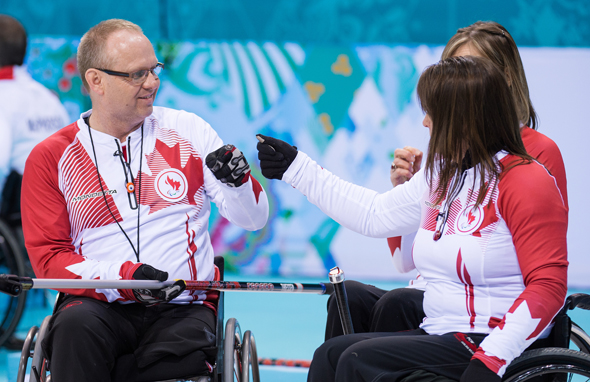 Sochi, RUSSIA - Mar 11 2014 -  Dennis Thiessen and Ina Forrest fist bump as Canada takes on China in Wheelchair Curling at the 2014 Paralympic Winter Games in Sochi, Russia.  (Photo: Matthew Murnaghan/Canadian Paralympic Committee)