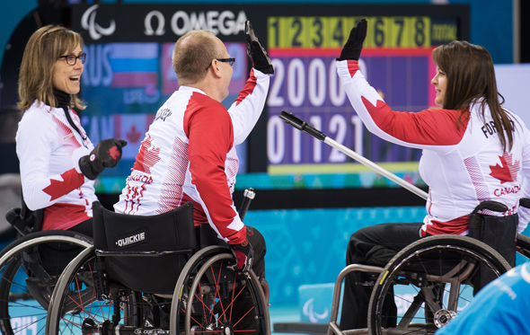 Sochi, RUSSIA - Mar 15 2014 - Sonja Gaudet, Dennis Thiessen and Ina Forrest give each other high waives as Canada takes on Russia in the Gold Medal Wheechair Curling match at the 2014 Paralympic Winter Games in Sochi, Russia.  (Photo: Matthew Murnaghan/Canadian Paralympic Committee)