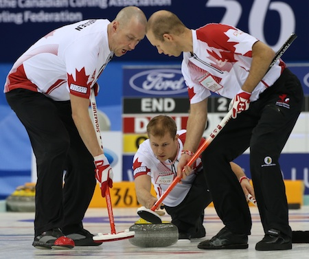 Team Canada sweepers Nolan Thiessen, left, and Pat Simmons go to work on Carter Rycroft's rock. Kevin Koe's Canadian posted a huge win over Germany on Thursday morning. (Photo, World Curling Federation/Richard Gray)