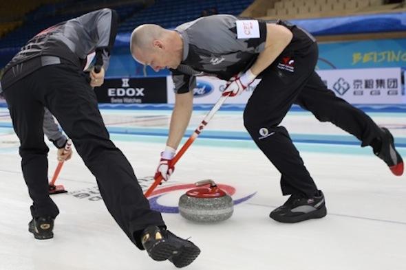 Équipe Canada balayeuse Nolan Thiessen, à droite, et Carter Rycroft travailler sur un rocher lors de la victoire de lundi. (Photo, Fédération mondiale de curling / Richard Gray)
