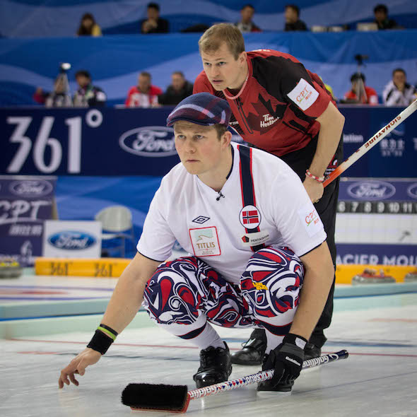 Norway's Christoffer Svae watches his shot as Canada's Carter Rycroft looks on. (Photo, World Curling Federation / Céline Stucki)