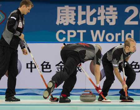 Carter Rycroft d'Équipe Canada, à gauche, supervise les efforts de balayage de Nolan Thiessen, milieu, et Pat Simmons. (Photo, Fédération mondiale de curling / Céline Stucki)