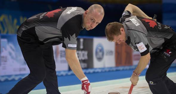 Équipe Canada balayeuses Nolan Thiessen, à gauche, et Carter Rycroft ont travaillé dur mercredi. (Photo, Fédération mondiale de curling / Céline Stucki)